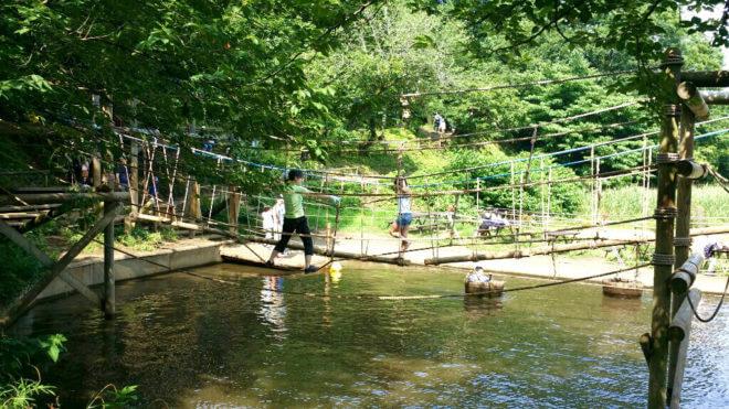 水上アスレチックのロープを渡る女性