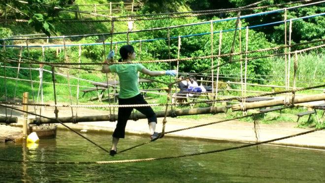 水上アスレチックのロープを渡る女性 アップ
