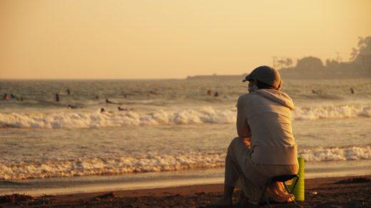 海辺で考えごとをする人の後ろ姿